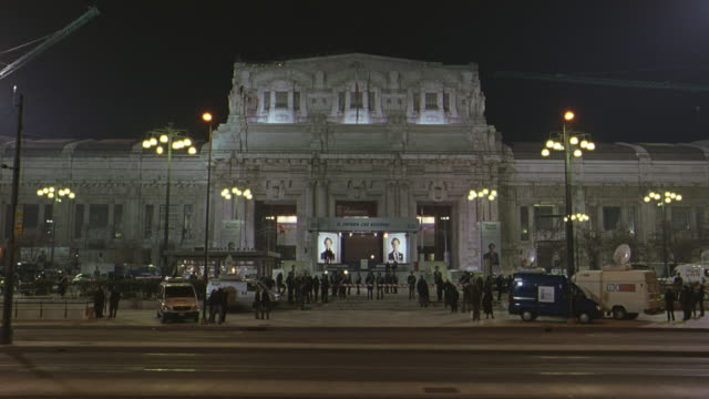 wide angle of central train station in milan. stage set up in front, could be for political rally. police barricades, news vans, people gathered outside. - station stock-videos und b-roll-filmmaterial