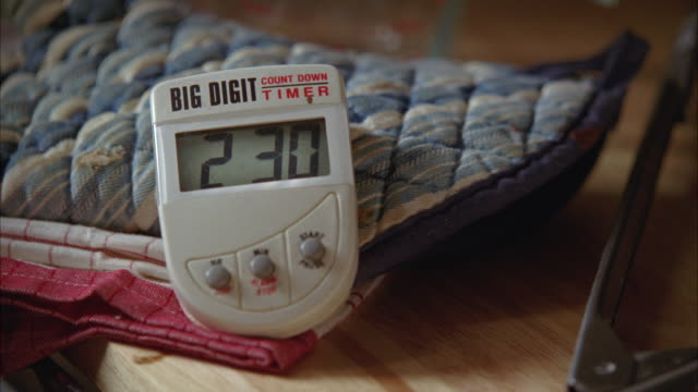 "vídeos de stock, filmes e b-roll de close angle of hand setting digital timer in kitchen. timers rests against oven mitts and dish towel counting down. tongs on counter next to timer. could be clock or alarm. could be baking or cooking. ""big digit"" timer. - setting clock"