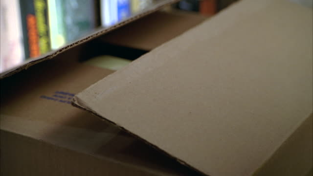 "close angle of cardboard box full of books. woman's hand places additional books in box and begin to tape box. box tapes shut. bookshelves in bg. hand writes ""cookbooks"" on box with black marker. - 段ボール箱点の映像素材/bロール"