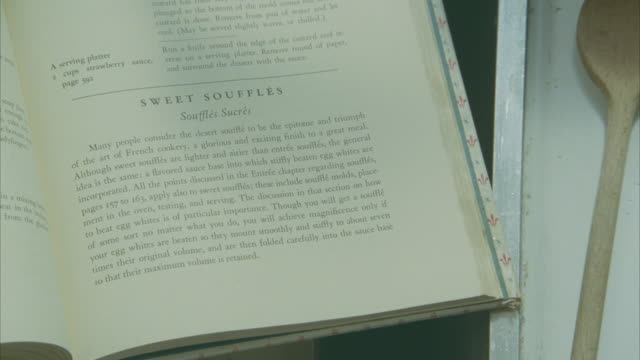 "close angle of julia child's ""mastering the art of french cooking"". displays recipe for ""sweet souffles"". wooden mixing spoon visible at right. kitchen. - recipe stock videos & royalty-free footage"