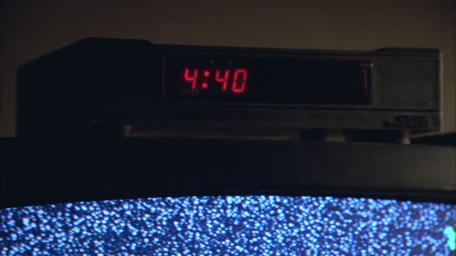 "close angle of a cable box with digital clock display on top of a television. static on tv screen then disappears. clock displays ""4:40"" likely am morning. - cable tv stock videos and b-roll footage"