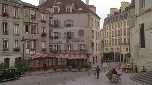 wide angle of a town square in paris, france circa 1949. cafes, restaurants, people walking in street, fruit and flower peddlers with cart, nuns and approaching cyclist visible. awning, middle class apartment buildings, car approaching. lamp posts. church - french restaurant stock videos & royalty-free footage