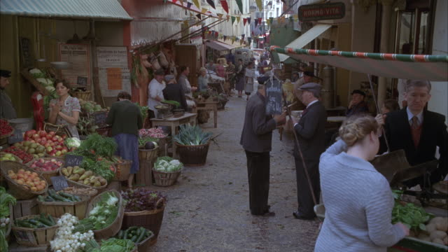 wide angle of a market or marketplace in paris, france, circa 1949. fruit and vegetable stands, people wearing forties period costumes. awnings and vendors visible. - 1949 stock videos & royalty-free footage