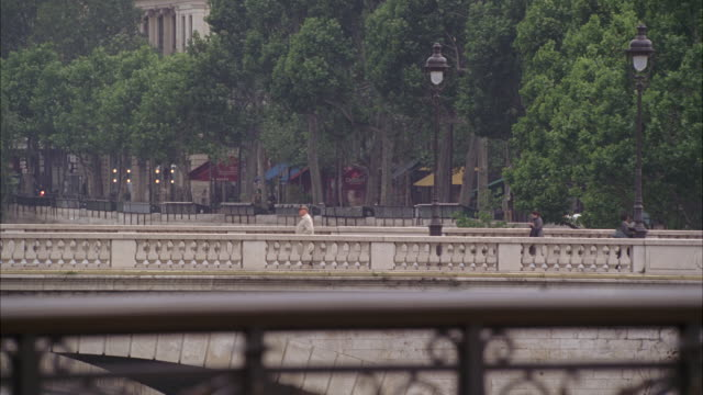 wide angle of a city street and bridge overpass on the seine river in paris, france. people walking, cars and bus visible. lamp posts, trees. - wide angle stock videos & royalty-free footage