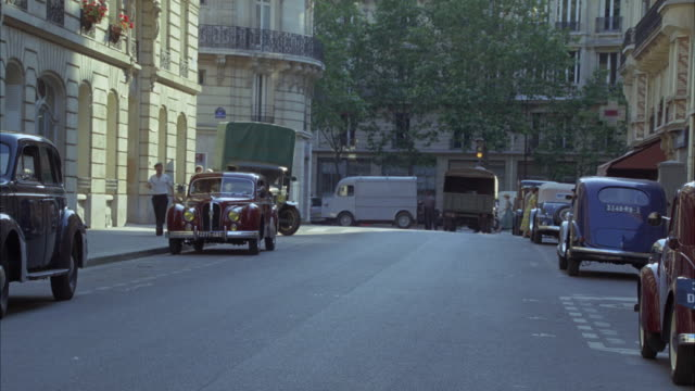 WIDE ANGLE OF CITY OR TOWN STREET, TOWN SQUARE IN PARIS, FRANCE CIRCA 1940S. TREES, MIDDLE TO UPPER CLASS APARTMENT BUILDINGS, VINTAGE CARS, INCLUDING A 1950 HOTCHKISS ANJOU, AT LEFT, IN FRONT OF GREEN TRUCK.