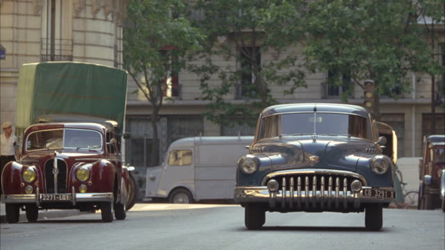 WIDE ANGLE OF 1940S VINTAGE CARS, INCLUDING A 1950 HOTCHKISS ANJOU, AT LEFT, IN FRONT OF GREEN TRUCK ON A CITY OR TOWN STREET. A 1950 BUICK ROADMASTER STATION WAGON DRIVES BY. CLIP ENDS WITH OTHER CARS OUT OF FOCUS. PEOPLE WALKING, BICYCLE, BABY CARRIAGE