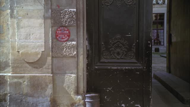 """medium angle of an old door on a street in paris, france. small no parking warning sign at left reads, """"sortie de voiture - priere de ne pas stationner"""". architecture. - no parking sign stock videos & royalty-free footage"""