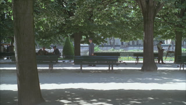 wide angle of a park with benches. could be 1940s or 1950s. two elderly men chatting on a park bench at left and a painting artist in period costume at right. man in suit with briefcase walks by. pigeons, trees, shadows. - 1940 1949 stock-videos und b-roll-filmmaterial