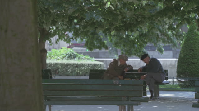stockvideo's en b-roll-footage met wide angle of a park. 1940s period costumes. could be modern day. two elderly men chatting on a park bench. man in suit with briefcase walks by. pigeons, trees visible. - 1940 1949
