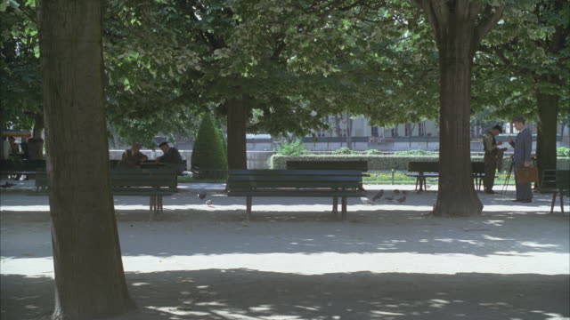 WIDE ANGLE OF A PARK WITH BENCHES. COULD BE 1940S OR 1950S. TWO ELDERLY MEN CHATTING ON A PARK BENCH AT LEFT AND A PAINTING ARTIST IN PERIOD COSTUME AT RIGHT. MAN IN SUIT WITH BRIEFCASE WALKS BY. PIGEONS, TREES, SHADOWS.