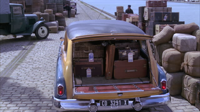 wide angle of a 1950 buick roadmaster station wagon loaded with older luggage from 1940s. two men, dock workers, load more bags before closing the trunk. barrels, cargo, cobblestones, old truck, port of harbor visible. travel. - 1940 1949 video stock e b–roll