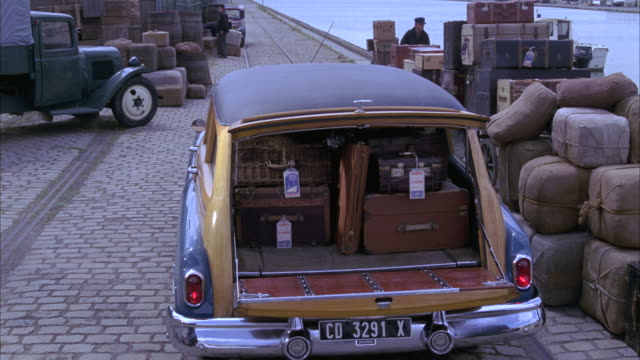 WIDE ANGLE OF A 1950 BUICK ROADMASTER STATION WAGON LOADED WITH OLDER LUGGAGE FROM 1940S. TWO MEN, DOCK WORKERS, LOAD MORE BAGS BEFORE CLOSING THE TRUNK. BARRELS, CARGO, COBBLESTONES,, OLD TRUCK, PORT OF HARBOR VISIBLE. TRAVEL.