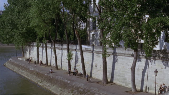WIDE ANGLE OF A PARIS RIVER BANK BY THE SEINE RIVER. TREES AND APARTMENT HOUSES VISIBLE, PEOPLE WALKING ALONG RIVERSIDE WALKWAY BELOW. MIDDLE TO UPPER CLASS. TOP OF VINTAGE CAR DRIVING BY VISIBLE IN BG. COULD BE 1940S PERIOD.