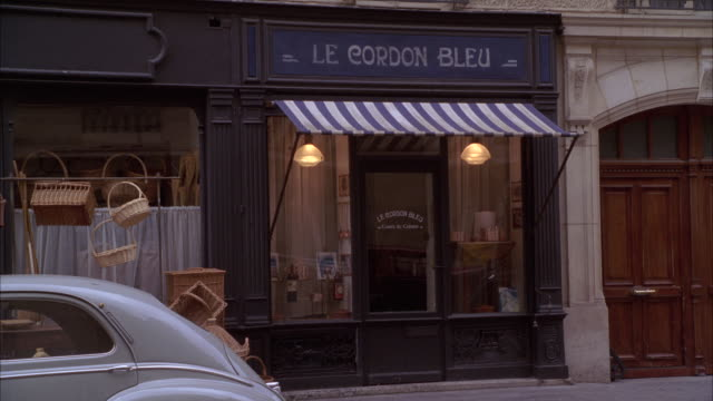 "WIDE ANGLE OF A BUILDING STOREFRONT WITH SIGN, ""LE CORDON BLEU"". COULD BE CULINARY SCHOOL, STORE, RESTAURANT, BISTRO, CAFE. TWO MEN IN 1940S PERIOD COSTUMES VISIBLE ON SIDEWALK. VINTAGE FORTIES CAR PARKED IN FG. BASKETS VISIBLE HANGING FROM WINDOW."