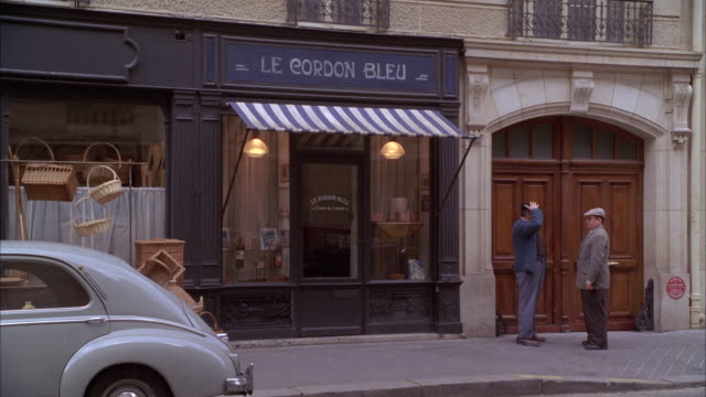 "wide angle of a building storefront with sign, ""le cordon bleu"". could be culinary school, store, restaurant, bistro, cafe. two men in 1940s period costumes visible on sidewalk. vintage forties car parked in fg. baskets visible hanging from window. - 1940 1949 stock-videos und b-roll-filmmaterial"