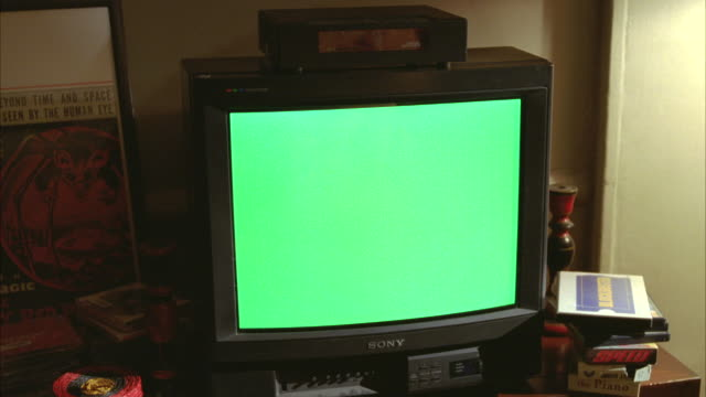 "medium angle of a sony television and green screen, with a small cable box sitting on top of tv. various vhs videocassette tapes visible, including a ""blockbuster"" box, movie titles, ""speed"" and ""the piano"". could be in living room, den, or family room. c - television chroma key stock videos & royalty-free footage"