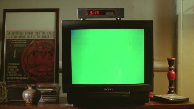 "medium angle of a sony television and green screen, with a small cable box sitting on top of tv. time on cable box shows ""9:15"". candle stick, pottery art piece, ""cinemagic"" poster visible. could be in living room, den, or family room. could be used for p - hd format stock videos & royalty-free footage"