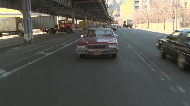 tracking shot 1979 cadillac coupe deville car driving on street under bridge. new york. cadillac pulls or tows porsche 911 targa car behind it. city visible in bg. bridges. - キャデラック点の映像素材/bロール