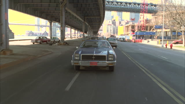tracking shot 1979 cadillac coupe deville car driving on street under bridge. new york. cadillac pulls or tows porsche 911 targa car behind it. city visible in bg. bridges. cadillac pulls of road. 1981 chevy impala car in fg. - underpass stock videos and b-roll footage