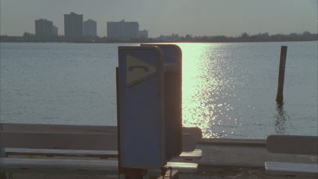 medium angle of telephone booth standing near benches by bay or harbor. condominiums or apartment building in bg. sun reflects off water. - pay phone stock videos and b-roll footage