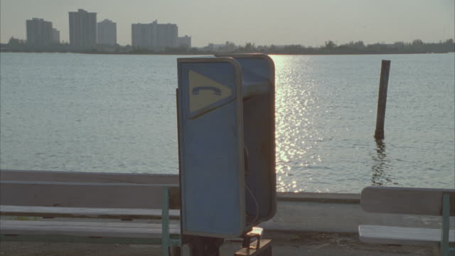 medium angle of telephone booth standing near benches by bay or harbor. condominiums or apartment building in bg. sun reflects off water. - telefonkiosk bildbanksvideor och videomaterial från bakom kulisserna