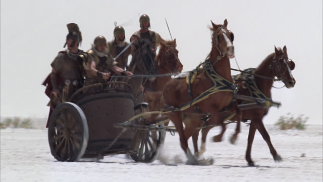 wide angle of roman soldiers or centurions on horse-drawn chariots. desert sand dunes. could be white sands new mexico. - cocchio video stock e b–roll