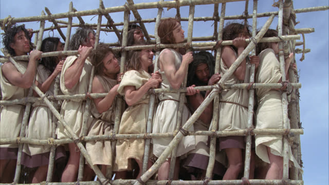 medium angle of slaves or prisoners locked in wooden cage struggling to escape. - trapped stock videos & royalty-free footage