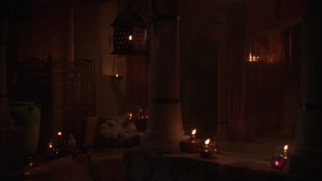 wide angle of roman bedroom in palace or castle. oil lamps burning. romantic. ancient. - bedroom stock videos & royalty-free footage