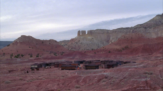 wide angle of tents in circle around campfire in middle the desert, could be a bedouin campsite. rocky hills and hoodoos in bg. could be in middle east. - ベドウィン族点の映像素材/bロール