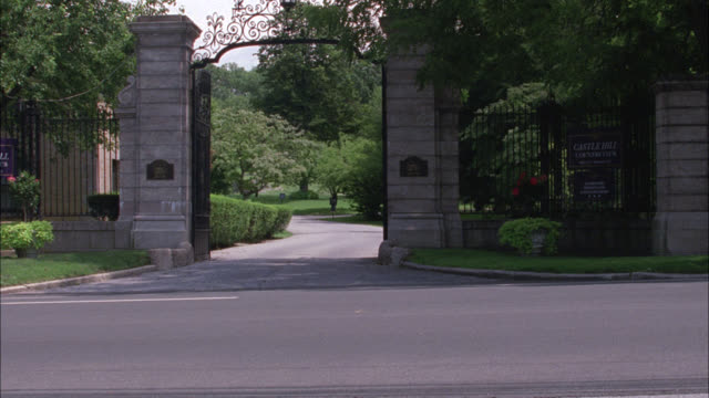 WIDE ANGLE OF GATE OR ENTRANCE TO UPPER CLASS HOME OR COUNTRY CLUB. TREES. COULD BE ESTATE, MANSIONS, OR MANOR.