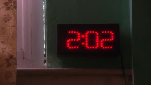 close angle of digital clock mounted on wall. - digital clock stock videos & royalty-free footage