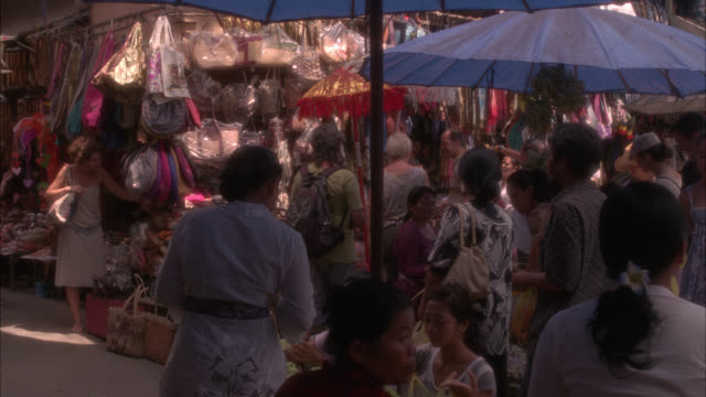 MEDIUM ANGLE OF PEOPLE SHOPPING IN MARKETPLACE OR BAZAAR. PURSES OR HANDBAGS HANGING FROM STAND IN BG. VENDORS.