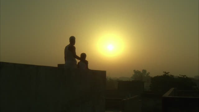 WIDE ANGLE OF MAN AND BOY, COULD BE FATHER AND SON, STANDING ON ROOFTOP WATCHING SUNSET. LOWER CLASS TOWN. HOPEFUL OR INSPIRATIONAL.