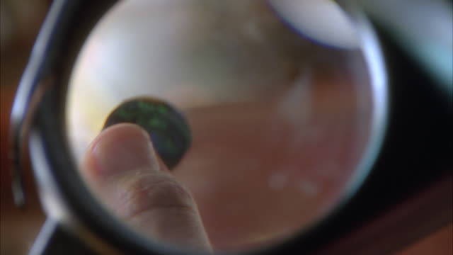 vídeos de stock e filmes b-roll de close angle pov through magnifying glass of person's hands, fingers holding a round piece of shell. could be for jewelry. - lupa