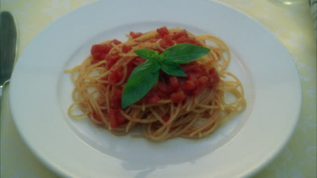 zoom in on plate of spaghetti or pasta. basil leaf garnish. food. - garnish stock videos & royalty-free footage