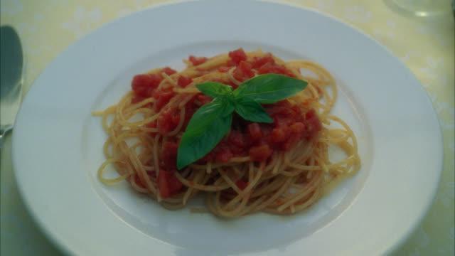 zoom in on plate of spaghetti or pasta. basil leaf garnish. food. fork. - garnish stock videos & royalty-free footage