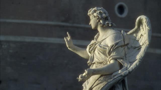 medium angle stone statue of angel on ponte sant'angelo. - ängel bildbanksvideor och videomaterial från bakom kulisserna