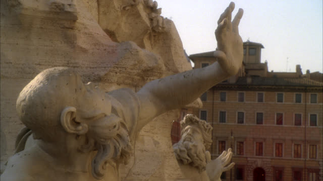 pan left to right of stone sculpture or statue on fountain of the four rivers in piazza navona. people and cafe or restaurant in bg. - piazza video stock e b–roll