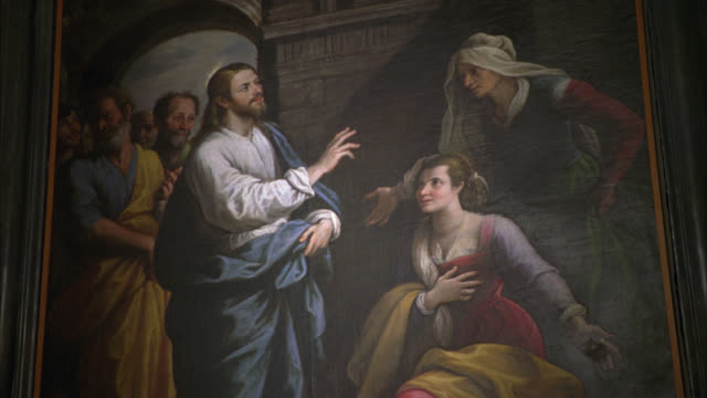 MEDIUM ANGLE OF RELIGIOUS PAINTING WITH JESUS CHRIST BLESSING WOMEN IN TEMPLE. MEN IN BG. COULD BE IN CHURCH.