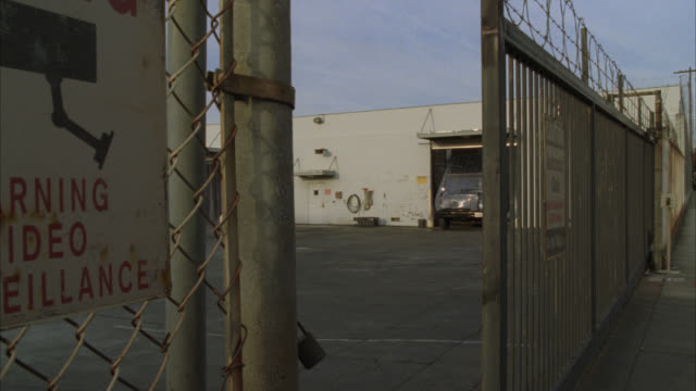 "medium angle of a barbed wire fence and gate. sign reads, ""caution automatic gate...gate closes after each vehicle... do not tailgate."" gate begins to open and several armored trucks pull out of the garage and leave the area. building could be warehouse o - tor konstruktion stock-videos und b-roll-filmmaterial"