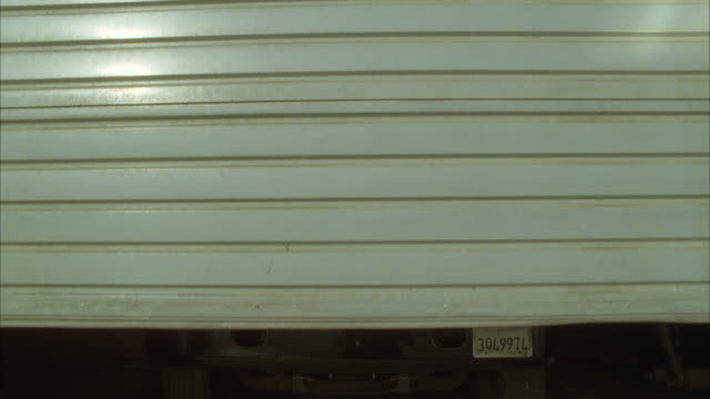 medium angle of a commercial garage door opening to reveal an armored car or truck. could be warehouse or industrial storage facility. - garage stock-videos und b-roll-filmmaterial