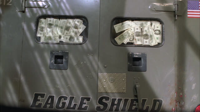 medium angle of an armored truck or car as seen from rear. us dollar bills seem to be taped to rear windows of truck. american flag visible on upper right of truck. money. currency. - armored vehicle stock videos & royalty-free footage