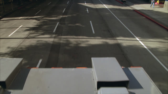 HIGH ANGLE DOWN MOVING POV OF ARMORED TRUCK DRIVING ON CITY STREET.