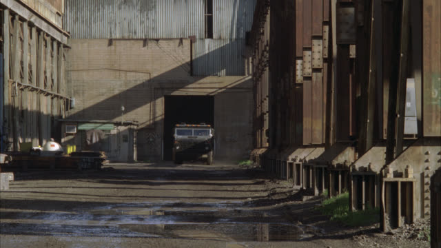 wide angle of armored truck driving through alley between industrial buildings or abandoned warehouses. industrial area. mud. - armoured vehicle stock videos and b-roll footage
