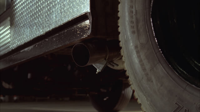 close angle of exhaust coming out of tailpipe of armored truck. truck begins to drive away. - armored truck stock videos and b-roll footage