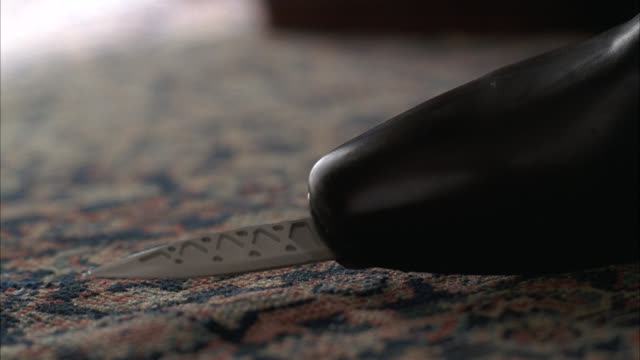 CLOSE ANGLE  TIP OF LEATHER BOOT WITH KNIFE HIDDEN IN SOLE OF SHOE. KNIFE POPS OUT AND BACK IN. SERIES. WOMAN'S SHOE, CARPETED FLOOR. SECRET WEAPON. SPY. ESPIONAGE.
