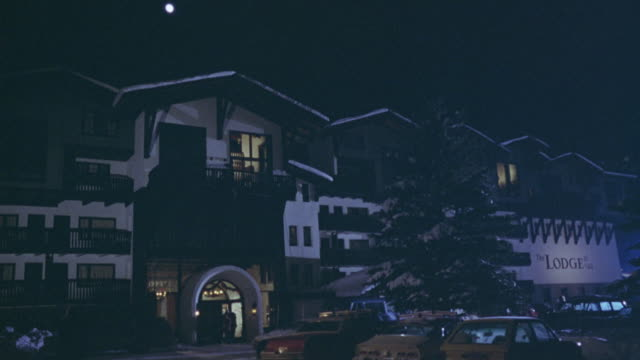 """WIDE ANGLE OF SKI RESORT AT NIGHT. SEE 'THE LODGE"""" WRITTEN ON SIGN. SNOW COVERED ROOF AND TREES. SEE DRIVEWAY IN FRONT."""