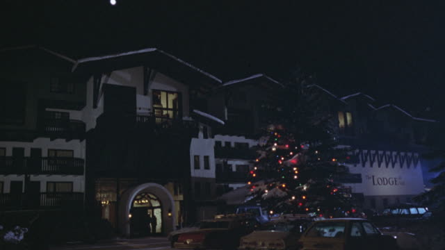 "wide angle of ski resort. see sign that says ""the lodge"" in front. christmas tree in front of lodge lit up. front driveway. - ski lodge stock videos & royalty-free footage"
