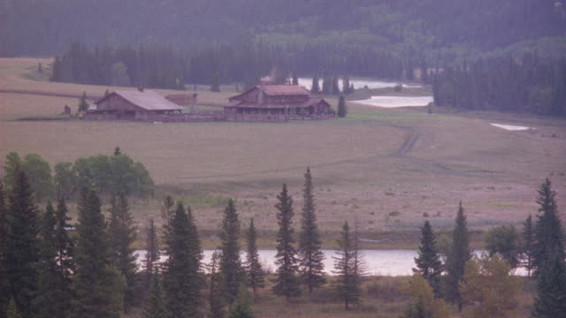 medium angle, see ranch house or large cabin and stable to left near banks of a river. see wheel tracks leading to cabin. land and forest in background. could be ranch or farm. see river and banks with trees in foreground, river continues around cabin at - barn stock videos & royalty-free footage