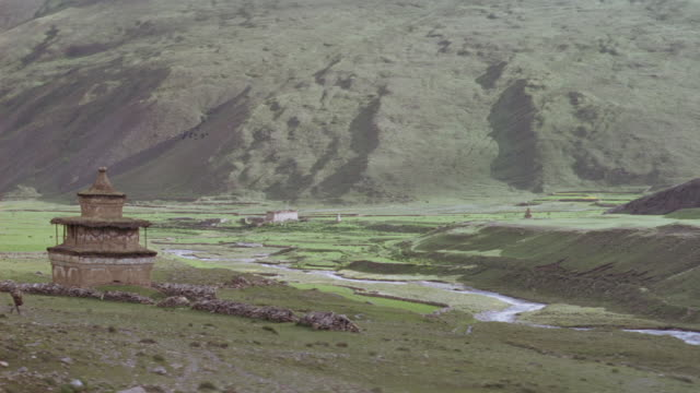 MEDIUM ANGLE OF FLOOR OF VALLEY WITH STREAM RUNNING IN CENTER. SEE SHRINE ON LEFT, TWO PEOPLE RUN TOWARD STREAM AND DUCK BEHIND ROW OF ROCKS, MAY BE PRINCIPAL ACTORS. HILL COVERED WITH GRASS IN BACKGROUND.
